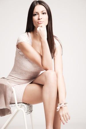 vestido corto: elegante mujer joven en vestido corto, sentarse en la silla, tiro del estudio