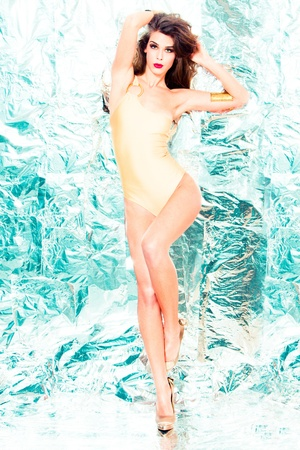 one piece: fashion model full body shot in one piece swimwear golden color, stand  in front  shiny background Stock Photo