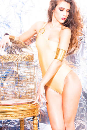 one piece: fashion model in one piece swimwear golden color, stand by golden birdcage in front of shiny background