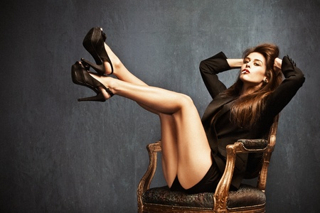 attractive woman in high heels, shorts and black tuxedo jacket sit on chair, cigarette in mouth, long brown hair, small amount of grain added photo
