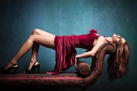 indoor shot: elegante mujer sensual joven en vestido rojo en el tiro interior Recamier