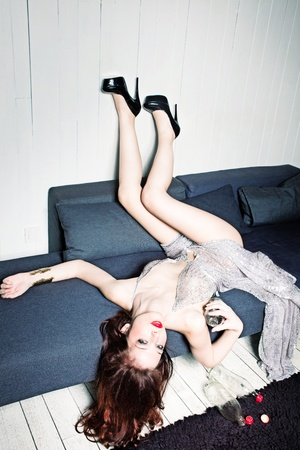 fashion woman in provocative dress lie on bed hold glass bottle, indoor shot photo