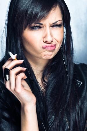malos habitos: mujer joven con el cigarrillo en la mano y la expresi�n de disgusto, tiro del estudio Foto de archivo