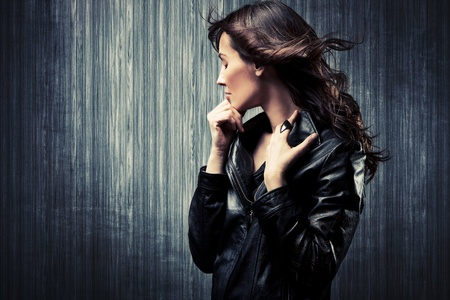 leather jacket: melancholy adult woman in black leather  jacket profile portrait