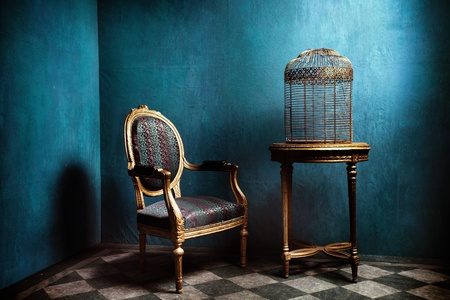 roundtable: Louis table, armchair and old golden bird cage in blue room with tiled floor