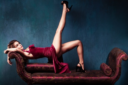 elegant woman in red dress and high heels lie on recamier   photo