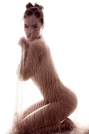 nude art model: beautiful nude young woman  covered with net, side view, full body shot, white studio