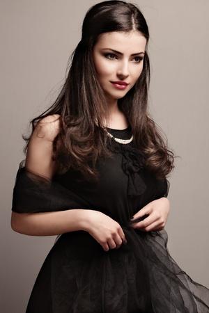 dress: stylish elegant woman in black dress wearing pearls, studio shot