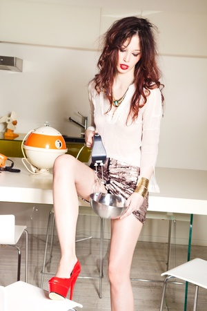 attractive woman in mini skirt with mixer in the kitchen photo