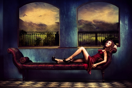 green couch: sensual woman in red dress lie on sofa in room with a view on mountains with rainy clouds