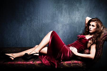 long sexy legs: sensual elegant young woman in red dress on recamier indoor shot Stock Photo