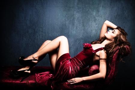 sexy beine: elegante sinnliche junge Frau im roten Kleid auf Recamier Innen-Schuss Lizenzfreie Bilder