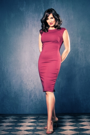 mujer elegante: elegante mujer madura en el vestido rojo ajustado, golpe al cuerpo completo, sala con paredes azules y piso de baldosas