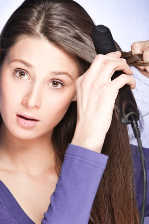young woman use hair straightener iron, studio shot Stock Photo - 13198043