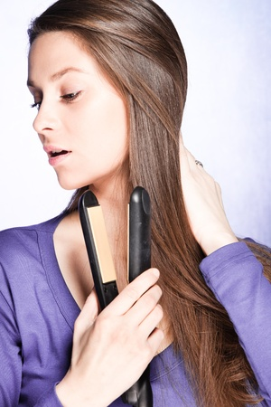 young brunette woman use hair straightener iron, studio shot photo