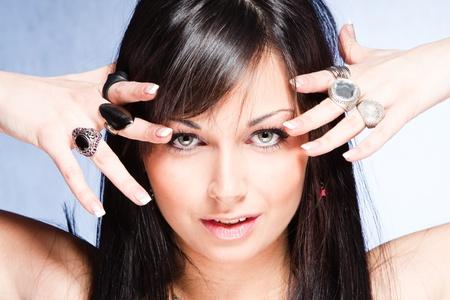 black hair blue eyes: blue eyes girl with lot of rings on hands, studio shot