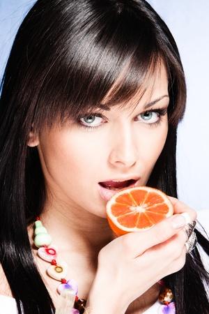 black hair blue eyes: blue eyes girl hold halfe of orange in hand looking at camera studio shot