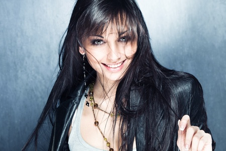 black hair blue eyes: smiling blue eyes young woman with healthy and shiny long hair in black leather jacket, studio shot