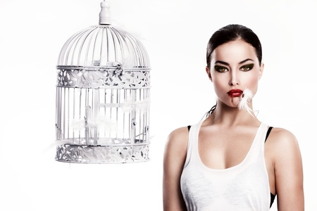 cat woman with feathers in mouth stand beside empty cage photo