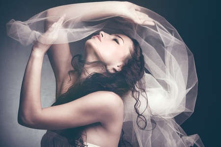 muse: beautiful young woman play with white veil profile studio shot