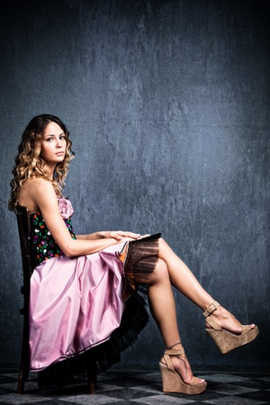 young  blond woman in elegant pink dress sit on chair in empty grunge room with tiled floor photo