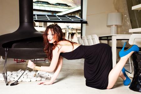 pelirrojas: la moda disparo de una bella modelo femenino en el largo vestido negro y zapatos de tacones altos en el moderno complejo de apartamentos Foto de archivo