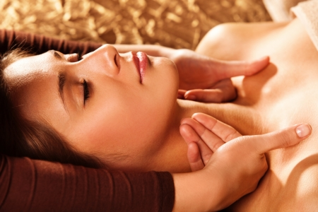 health resort treatment: woman getting neck and face  massage in spa salon