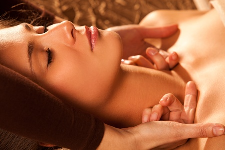 woman getting neck and face  massage in spa salon photo