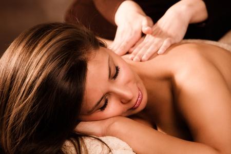 face massage: woman enjoy in back massage in spa salon