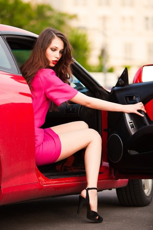 out door: sensual stylish woman in pink dress get out from car