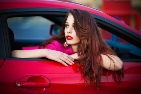 long red hair woman: fashion woman in red sport car portrait