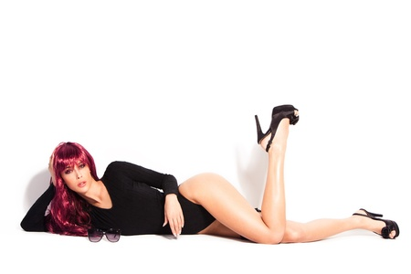 cuerpo entero: mujer atractiva con peluca roja siempre en ropa interior de cuerpo negro y tacones altos, acostarse, tiro de todo el cuerpo, blanco de estudio