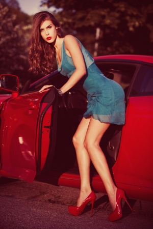attractive woman get out of car, retro look colors, small amount of grain added photo