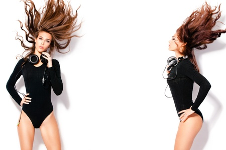 dancing woman: attractive women with headphones in dancing motion, hair fly, wearing tight black body, studio white Stock Photo