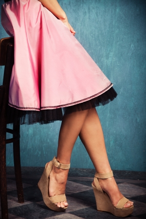 female legs in wedge high heel shoes and romantic pink skirt photo