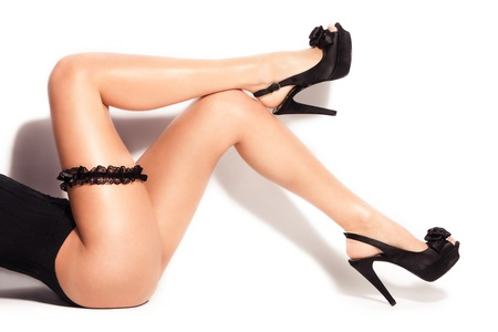 high heels woman: smooth perfect woman legs in high heels and butt strap, studio white Stock Photo