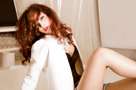 sensual redhead woman in white jacket, indoor shot Stock Photo