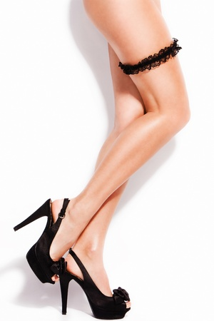 smooth perfect woman legs in high heels and butt strap, studio white photo