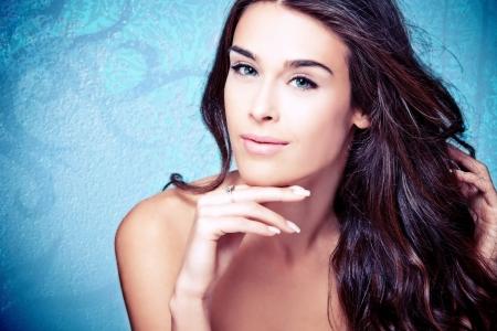 mooie vrouwen: jonge blauwe ogen brunette schoonheid vrouw portret op blauwe achtergrond Stockfoto