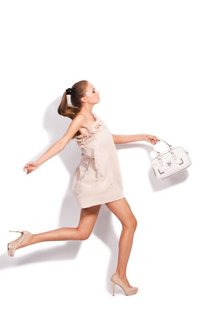 young woman in elegant short dress and high heel shoes run carrying hand-bag, studio white photo