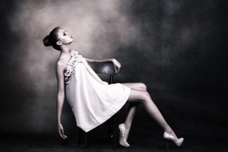 full body shot: young woman with bun styled hair in elegant dress pose on chair, studio shot Stock Photo