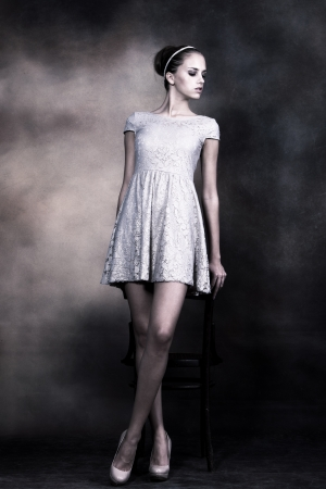 young gentle woman with bun styled hair in delicate lacy dress, full body shot,