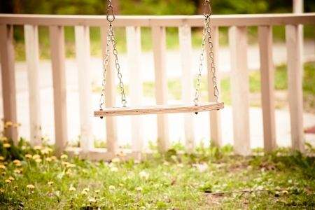 empty swing in backyard summer day photo