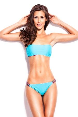 bikini bleu: jeune femme souriante en bikini tir studio de bleu