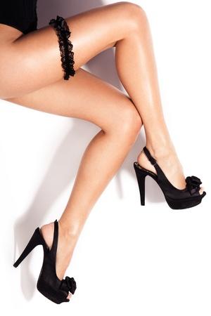 heel strap: long slim female legs in high heel  shoes and butt strap studio white