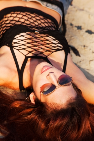 young woman with sunglasses lie on sand summer day sunset photo