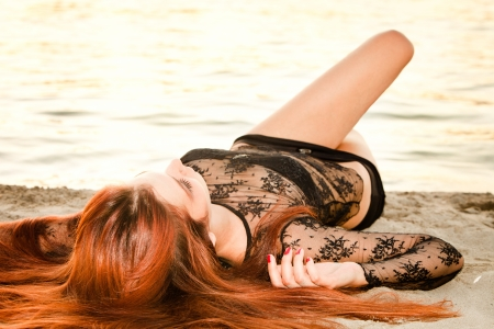 young redhead woman lie on sand beach summer day photo