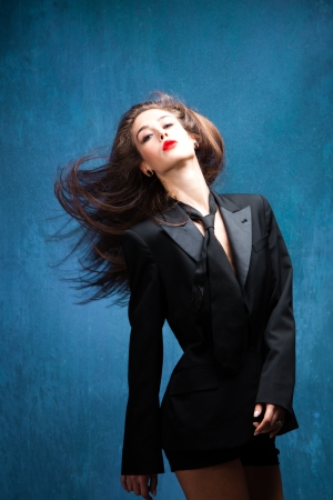 young woman in black tuxedo and tie with head in motion studio shot photo