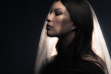 woman covered with black veil portrait, studio shot