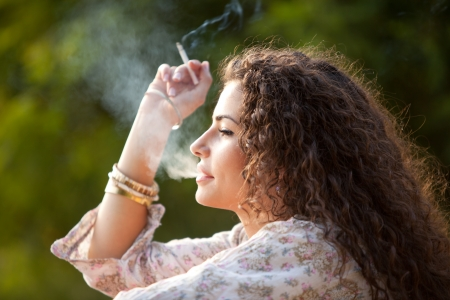 women smoking: young woman smoking outdoor shot, summer day in park Stock Photo